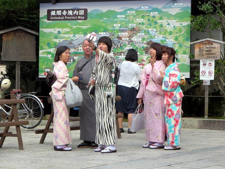 Japanese tourists taking selfies near Ginkakuji Temple in Kyoto, Japan.