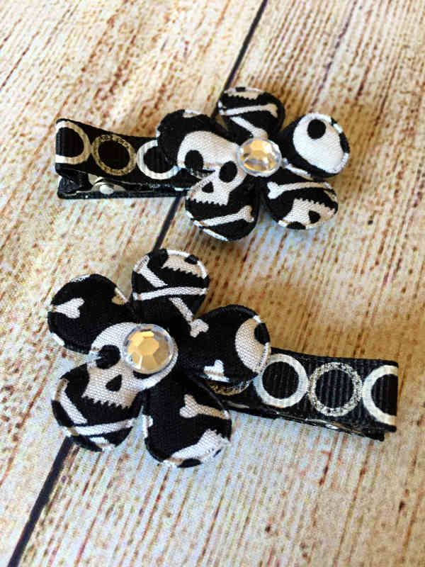 Add a little funky flair to your outfit with this set of Halloween hair clips.  Clips are fully lined with ribbon and have non slip grips to keep them in place.  This set features black, skull print flowers with gem centers on black, white and silver circle print ribbon.  These clips are made as a set.