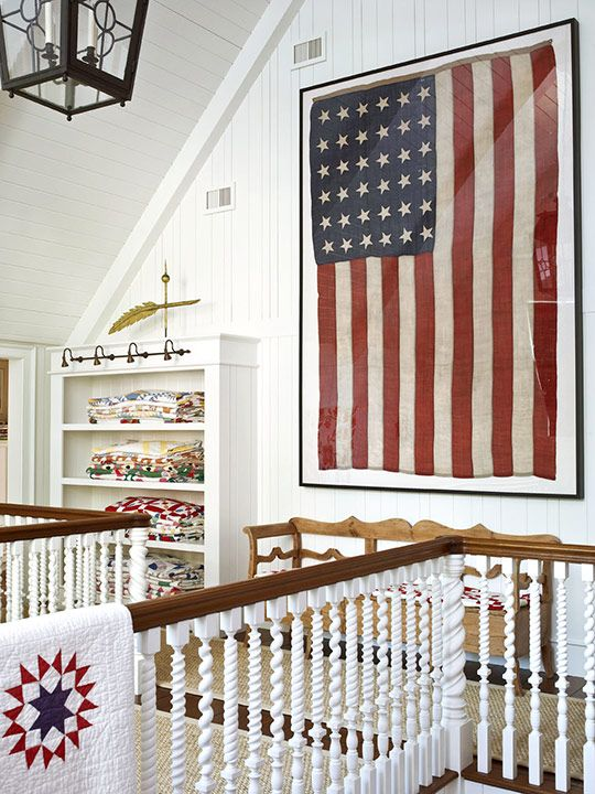 Heirloom quilts are stacked alongside a 36-star flag and antique pine bench on this second-level landing - Traditional Home®