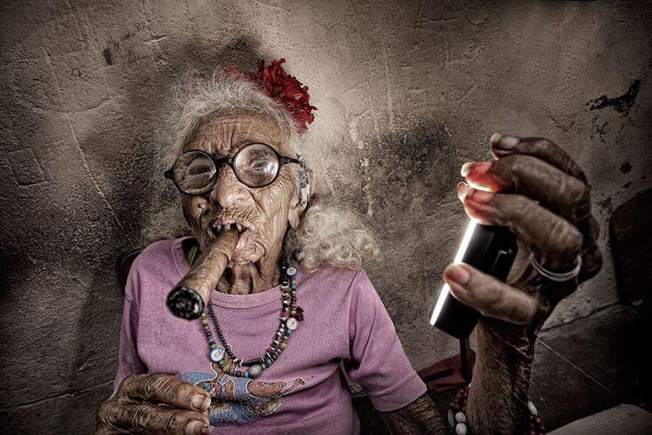 Une vieille cubaine fumant un cigare et tenant un flash annulaire