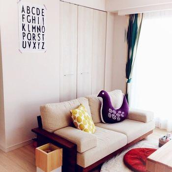 鳥のクッションがかわいいワンポイントになったお部屋。 ファブリックにいろいろな色を使っても、壁やソファ、ラグが白で統一されているのでごちゃごちゃしていません。