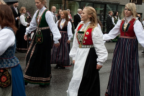 women dancing during a Syttende Mai celebration - Three of the bunads are from Sunnfjord, the other one is from Nordhordland. The blue one in the left corner is from Sør-Trøndelag.