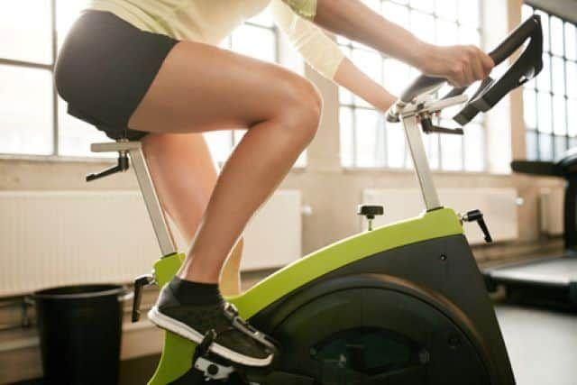 Devojka vozi bicikl u teretani