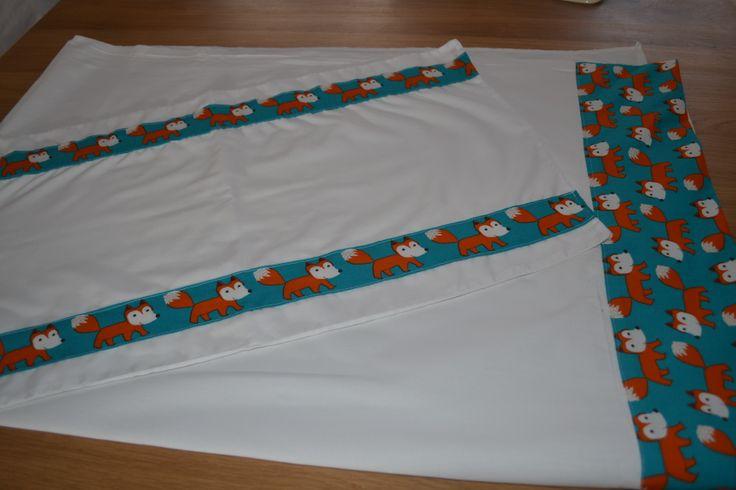 'Nieuw' katoenen laken en kussensloop voor babybed. (Oude boorden werden verwijderd en met een fris nieuw stofje werd een nieuwe boord gemaakt op de oude witte lakens die nog niet versleten waren.) Afmeting: 100cmx150cm.