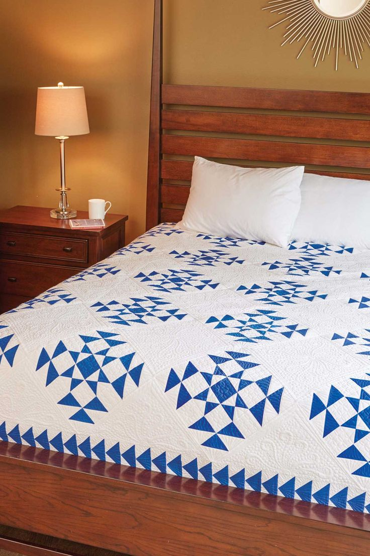 Liz Porter designed and made Corona Del Mar, a traditional two-color quilt, with open spaces for special quilting. Flying Geese units surround the quilt blocks for a perfect finish.