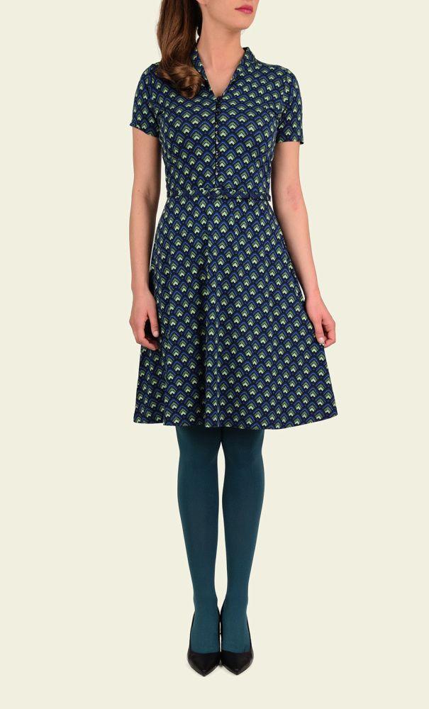 Dit vrouwelijke model heeft een comfortabele fit door de rekbare stof en wijd uitlopende rok. De jurk heeft een Art Decoprint en combineer je makkelijk met een Cocoon Cardigan. Opvallende details zijn de lange knoopsluiting en het sjaalkraagje.