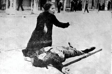 """Thessaloniki, Greece, May 9, 1936. A newspaper photo: Government troops just shot on to the striking tobacco workers; Tassos Toussis lays dead on a wooden door pannel, his mother crying above her son's body. Yannis Ritsos, shocked by this photo wrote during the 2 following days """"Epitaphios"""". Mikis Theodorakis composed music to accompany this poem by Ritsos."""