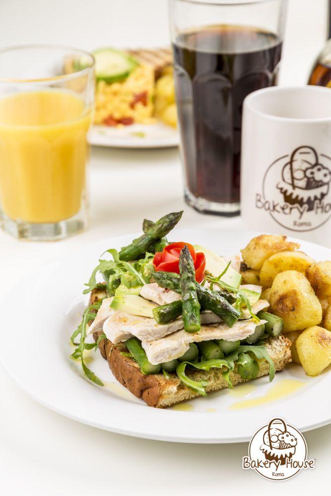Avocado Chicken Asparagus Tartine. Petto di pollo grigliato su un letto di pane all'avena tostato, olio d'oliva, limone, rughetta e asparagi con contorno di chips di patate.