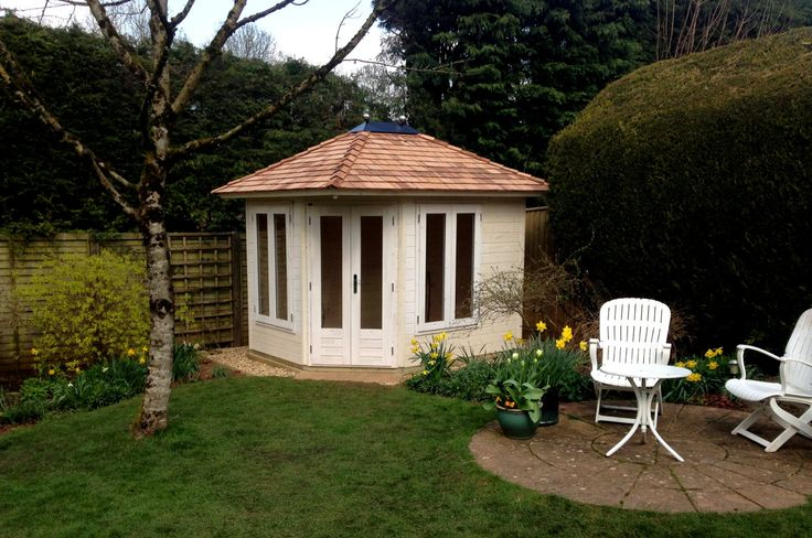 Corner Summerhouse with cedar shingle roof painted cream.