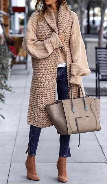 She wears a brown and wool coat, plain blue jeans, brown and leather shoes.