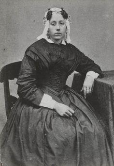 Vrouw in Terschellinger streekdracht. De vrouw is gekleed in zondagse dracht. Ze draagt een 'kleedje' (japon) en over het oorijzer de 'kap'. Op het voorhoofd draagt ze twee valse haarlokken. ca 1870 #Terschelling