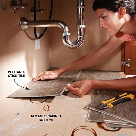 Put peel & stick tile under your sink cabinets. Protects and covers old stains. And easy to clean!