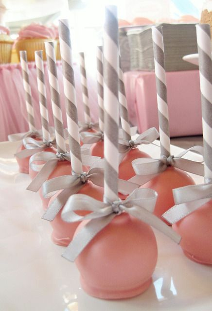 pretty pink cake pops - I love that they used stripe straws for the pop sticks!