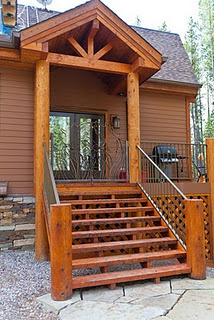 Notice the wrought iron bear gate with the moose head motif! Log posts and timbers make this side entrance pop.