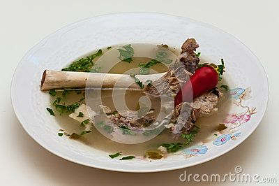 Lamb bone borsch on plate, with red pepper and green fresh lovage.
