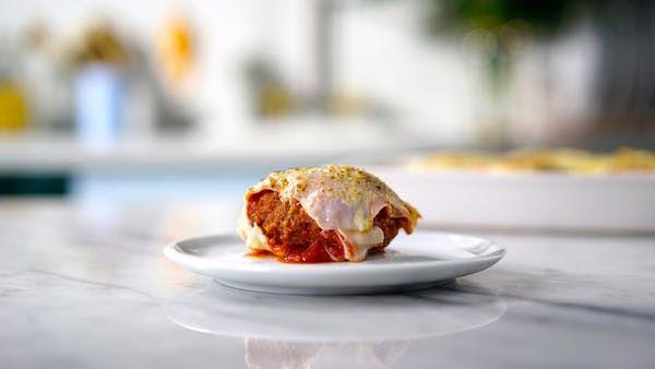 Receita com instruções em vídeo: Esse irresistível polpetone à parmegiana é tudo o que você precisa ver hoje!  Ingredientes: 500g de carne moída, Sal, Pimenta do reino, 2 colheres de sopa de creme de cebola, Folhas de manjericão a gosto, 2 ovos , 1 fatia de pão esmigalhado, 150 g de queijo muçarela cortado em cubos, 1 xícara de farinha de trigo, 1 xícara de farinha de rosca ou panko, 2 xícaras de molho de tomate, Folhas de manjericão para temperar, 150g de presunto em fatias, 200g de queijo…