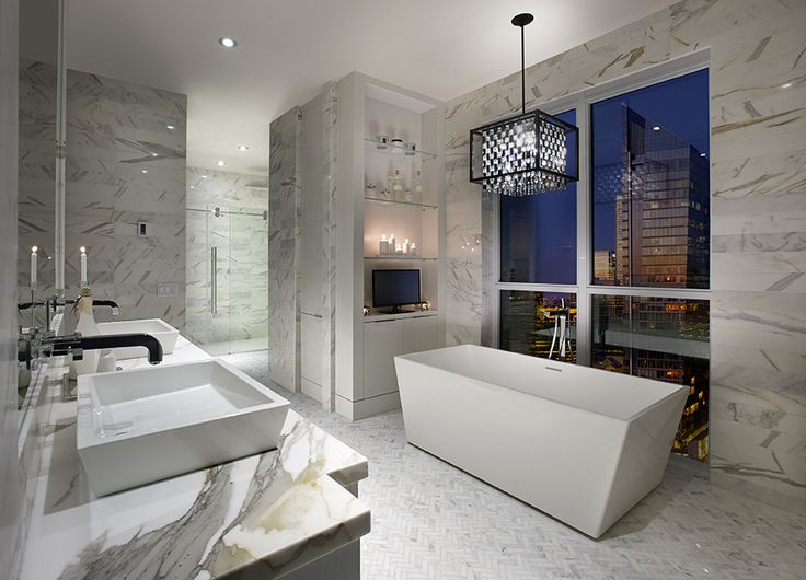 Spacious Master Ensuite with luxurious free-standing bathtub overlooking the Toronto Skyline. #TOSkyline.  WET Style Cube sink #wetstyle. Hansgrohe Axor wall mounted faucets #hansgrohe.  Marble countertop by Ciot #ciotcanada. Polished marble tiles on floor and wall by Saltillo Imports #Saltillo. #trideldesign #marble #bathroomdesign #300Front #atmosphere