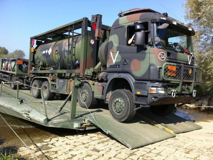 Legervoertuigen steken de IJssel bij Olst over via een pontonbrug.