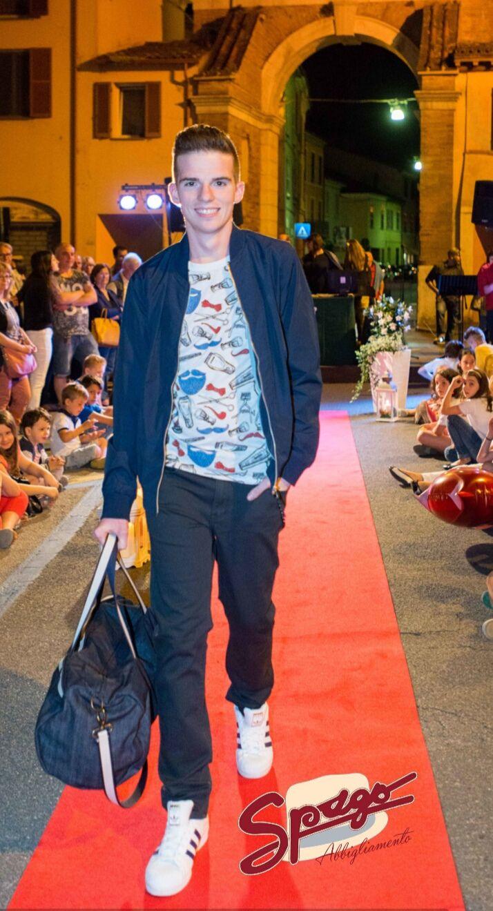 Francesco sfila con un pantalone in tela jeans della Globe, impreziosito da una catena GL _ officinacreazioni. T-shirt fantasia del brand ItalianLab e una giacca a vento di JACK & JONES. Il borsone da palestra è tutto italiano.  #SpagoAbbigliamento #AbbigliamentoUomo #SpagoUomo #AccessoriUomo #Accessori #Sfilata #SfilataUomo #Runway #BorgoSanRocco #MenRunway Ravenna24Ore Abbigliamento Uomo Ravenna RavennaToday