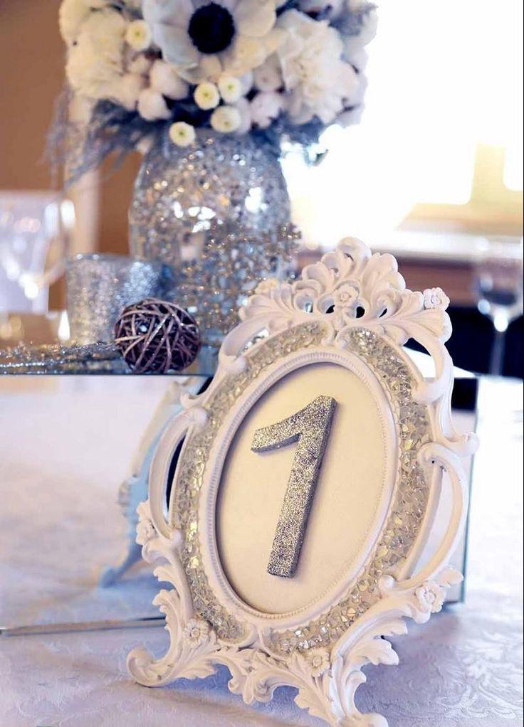déco mariage hiver en blanc et argent - bouquet d'anémones blanches en vase argenté, numéro de table vintage en blanc décoré de paillettes de couleur argent