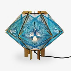 North For The Summer Andromeda Lighting Series is part sculpture and part lamp. Intricately woven string criss crosses between a wooden frame making colorful geometric patterns.