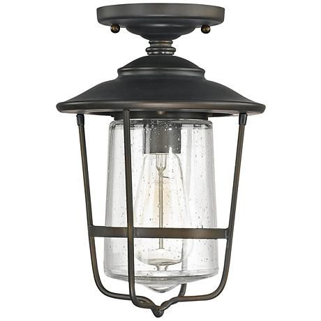 Turn an outdoor ceiling into a display space for chic industrial lighting with this steel and glass exterior fixture.This Old Bronze finish, semi-flush outdoor ceiling light has an easy, casual, transitional style with hints of industrial inspiration. A single nostalgic bulb is encased by a clear seeded glass jar that mimics the shape of the protective steel cage that surrounds it. A versatile design that will complement many styles of home exteriors, from Capital Lighting. Designed in…