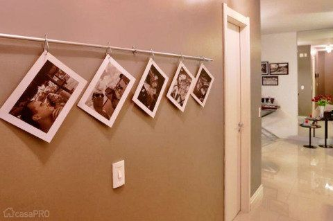 Com uma ideia super simples, porém original, este corredor acabou ganhando uma graça toda especial. Fotos impressas em adesivo vinílico texturizado foram aplicadas em plaquinhas de poliestireno presas por ganchos em um varão cromado fininho, daqueles que utilizamos em cortinas delicadas. Projeto de Aline Dal´Pizzol.