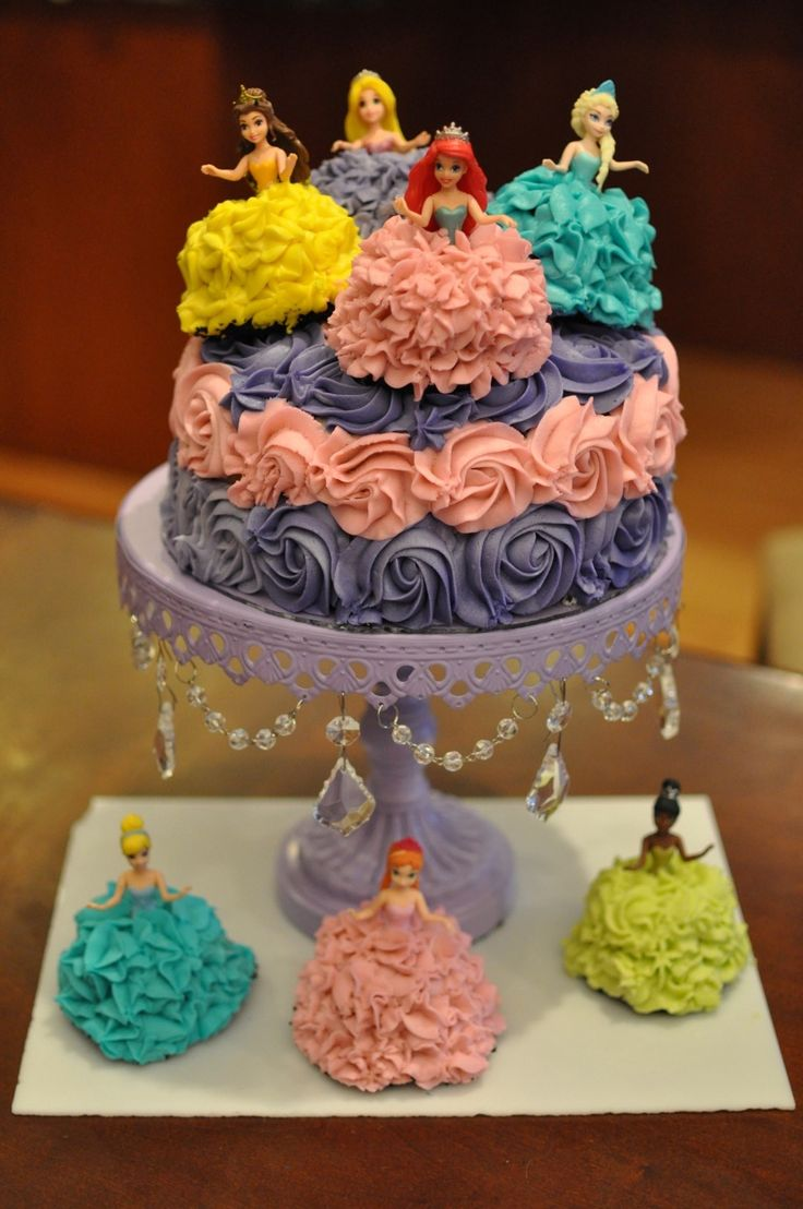 Disney Frozen princess cake and cupcakes with Ariel, Elsa, Rapunzel, Belle, Cinderella, Anna, and Tiana. I wrapped the legs of  Magiclip dolls in plastic wrap, then placed the dolls into inverted cupcakes. I used a Wilton 1M tip and buttercream to pipe the princesses' dresses and the rosettes on the cake.