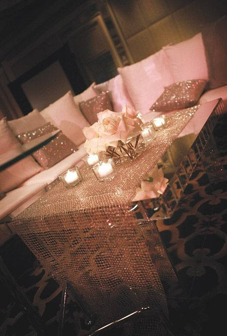 Chic lounge with white sofas, beaded pillows, mirrored tables, and centerpieces of floating candles. Absolute stunning