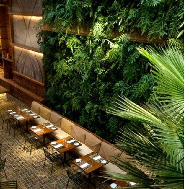 Jardim vertical, mesa com cadeiras, piso quadriculado. A ambientação do restaurante KAA, no Itaim (SP). Projetado por Artur Matos Casas, um dos destaques do projeto é a sensação de um amplo jardim. Paisagismo por Gil Fialho.