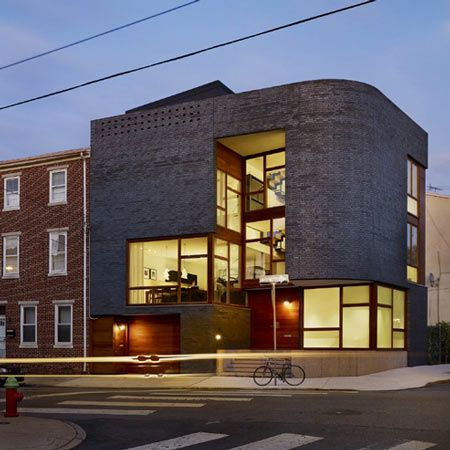 A house in Philadelphia that features a glazed interior wrapped in a curved brick facade.