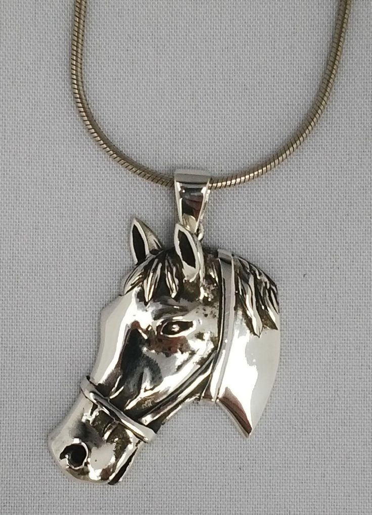 Sterling silver pendant of a horse head with detail.