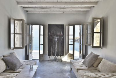 Dans le petit salon, partout l'oeil s'échappe sur la mer... Le décor y est minimal, avec des matelas en lin blanc posés sur de simples banquettes en bois et la réplique des porte-cierges orthodoxes esquissée à la craie par Manolis sur le mur peint en noir.