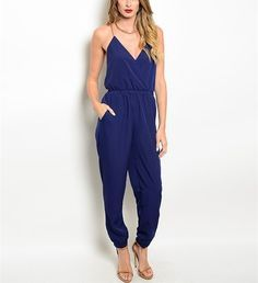 This spaghetti strap jumpsuit features a wrapped bodice, gathered waist and hidden pockets. Has a dropped inseam.