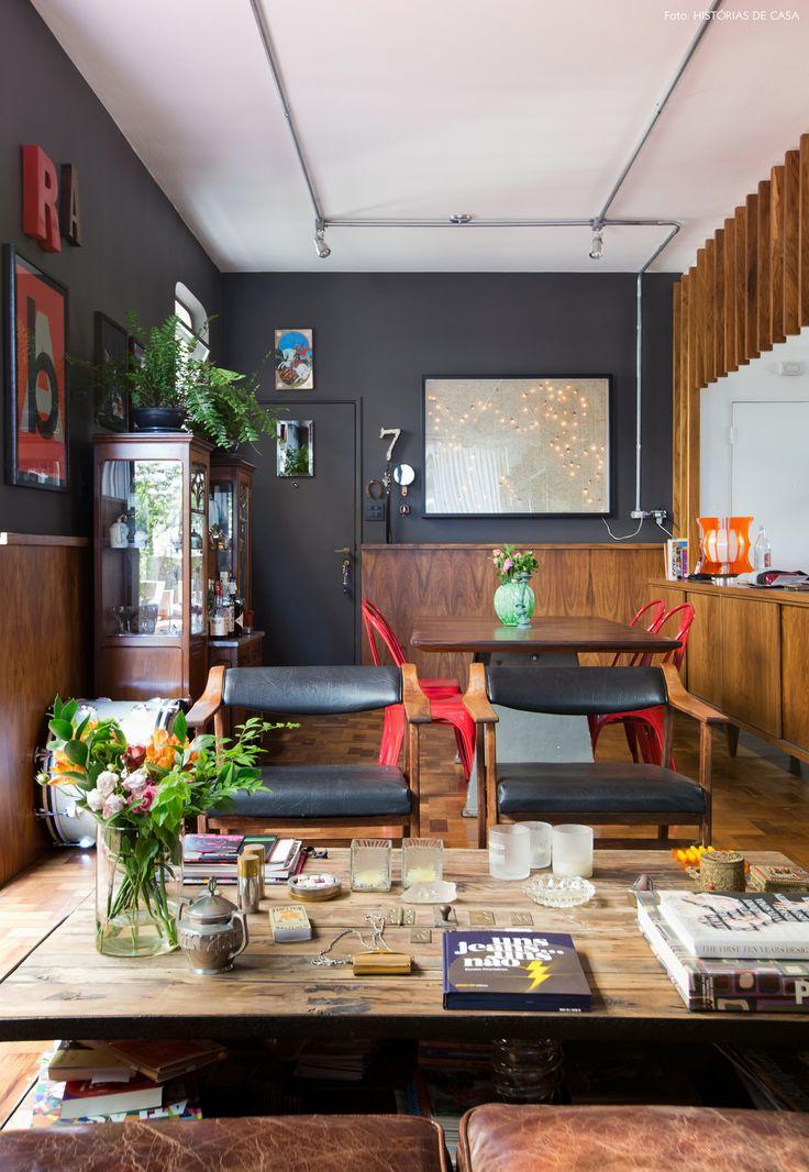 Sala de jantar com paredes pretas, muita madeira e móveis com estilo industrial.