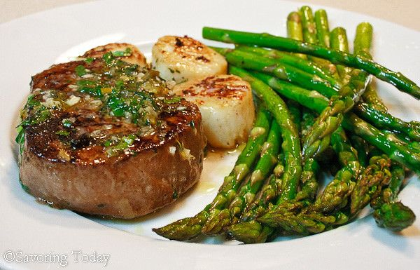 Create a romantic dinner at home for two with tenderloin steak seared in butter with scallops in subtle accents of lemon zest, white wine, garlic, and fresh basil.