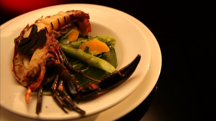 Baked marron in citrus sauce with asparagus, orange and truffle salad
