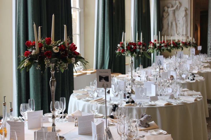 Candelabras at Woburn sculpture gallery red tulips white tulips ranunculus.  Wedding flowers at Woburn sculpture gallery