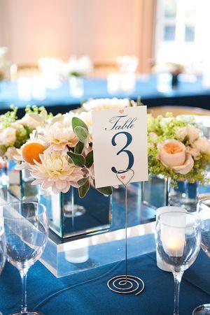 Blue tablecloths with peach floral arrangements
