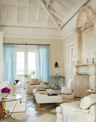 Architect Clemens Bruns Schaub designed Hilary and Galen Weston's Windsor, Florida, house; John Stefanidis handled the decor. Candy-striped tulle curtains brighten the living room, where a monumental fireplace and overmantel of carved Mexican shell stone fills a wall; the seating and embroidered fire screen are by Stefanidis   archdigest.com
