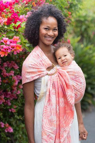 Baby Tula's Heliconia Tropics - Wrap Conversion Ring Sling Baby Carrier. 'Heliconia' Tropics is unique lush design with a fresh feel! 'Heliconia' Tropics has a design with a myriad of tropical flora that creates an elegant, lively repeating pattern. Its shades of peach, coral and white intertwine in a tactile tri-weave that provides texture, vibrant details, and soft pillow-like cush. 'Heliconia' ring slings are available in a variety sizes and adjust to fit your growing baby.