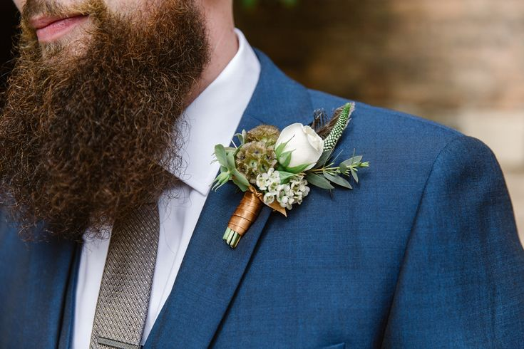 Wild flower and pheasant feather button hole. Photography by Natalie J Weddings