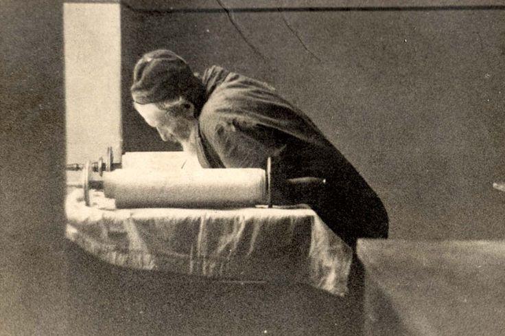 Jewish man bending over Torah scroll in the Lodz Ghetto