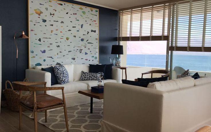 Muro en color azul navy o marino que contrasta con gran cuadro de Pablo Rodríguez Blanco. Diseñamos dos sofás idénticos blancos en mezclilla y los pusimos frente a frente, separados por una mesa de centro hecho de durmiente de tronco. Persianas de bambú,