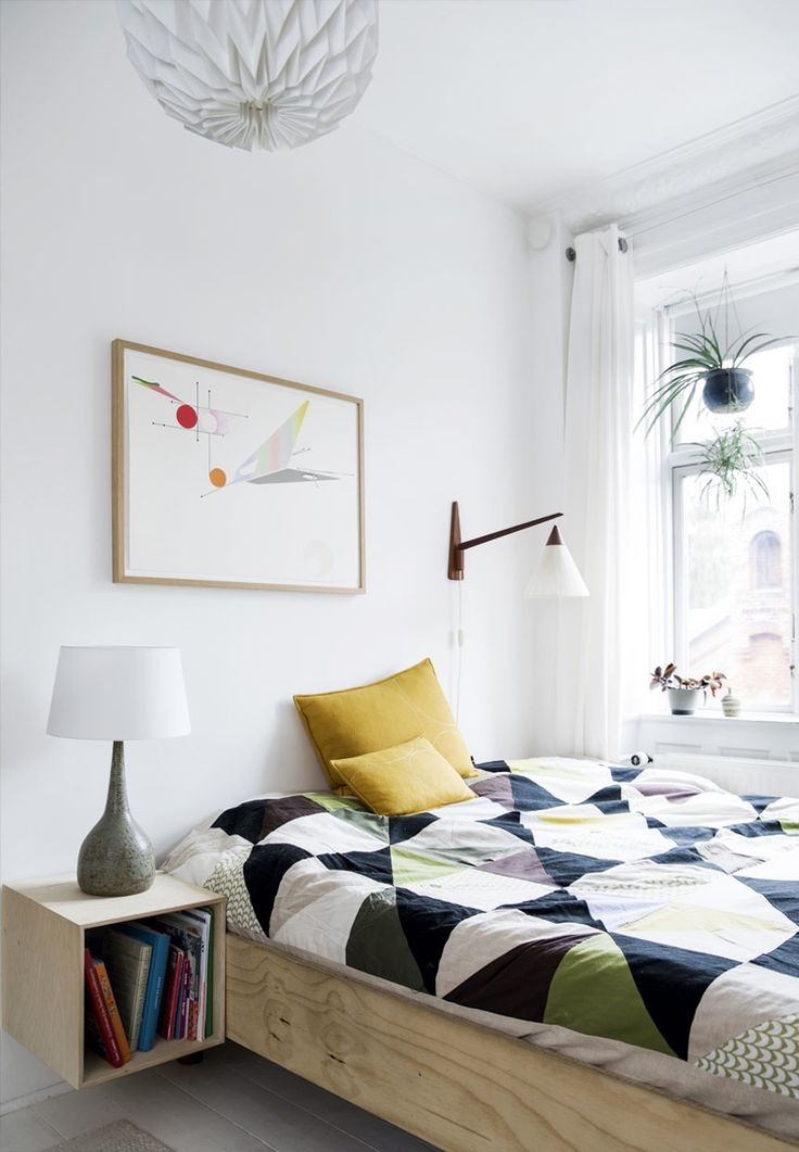 Bright bedroom with a wooden DIY bed frame and a colorful bedspread.