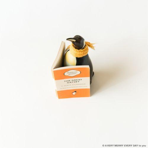 Penguin Books Launch...  Penguin Books Launch UK  月30日はイギリスロンドンの出版社 ペンギンブックスの設立記念日です Launchはたちあげの意味ですね  そういうわけでストレートに ペンギンがペンギンブックスの本を読んでいる写真です  この本の装丁にもペンギンが描かれていますよね デザインがかわいいので マグカップとかノートとかグッズも出ているんですよ  本を読んでいるのは 陶器製のペンギンの貯金箱なんです 北欧の銀行でもらえるキャラクターの貯金箱で わりと古いものです 口座を開くともらえるノベルティだったのかも もともとは赤いマフラーをしていたのですが 本の色に合わせてこのマフラーをつけかえました  ペンギンが読んでいるのはTHE GREAT GATSBY 華麗なるギャツビーですね 岡尾美代子
