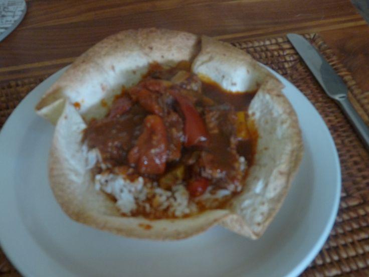 chilistoofvlees met rijst in een bakje van tortilla:de chili bestaat uit stoofvlees, 1 el kaneel, 1 el komijn, 1el paprikapoeder, 1 el oregano, beetje laurier, 2 gele paprika's, blik tomaten in blik en 4 tros tomaten, chili vlokken, 2 rode uien, koriander. dan potje guacamole saus erbij serveren of zelf maken en rijst koken. Ongev. 2,5 uur sudderen de chili, tot het vlees uit elkaar valt. Bakje kun je ruim van de voren maken.