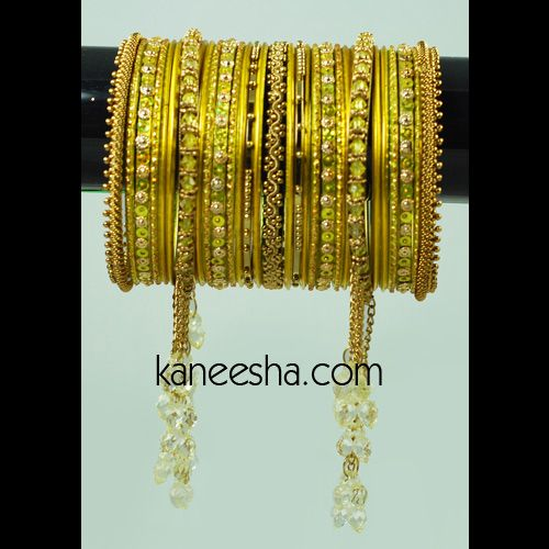 Fashion Bangle Set in a Striking Combination of Gold and Lime Green Accessorize your favorite outfit with these radiant bangles to look your best. The fiery golden fashion bangles are emphasized with a tinge of lime green. The bright golden bangles are accentuated with lime green crystals. The hanging golden tassels look phenomenal. This exuberant set of bangles is an expression of festivity and celebration.  Available Sizes: 2.8  #FashionBangleSet #LatestFashionBangles