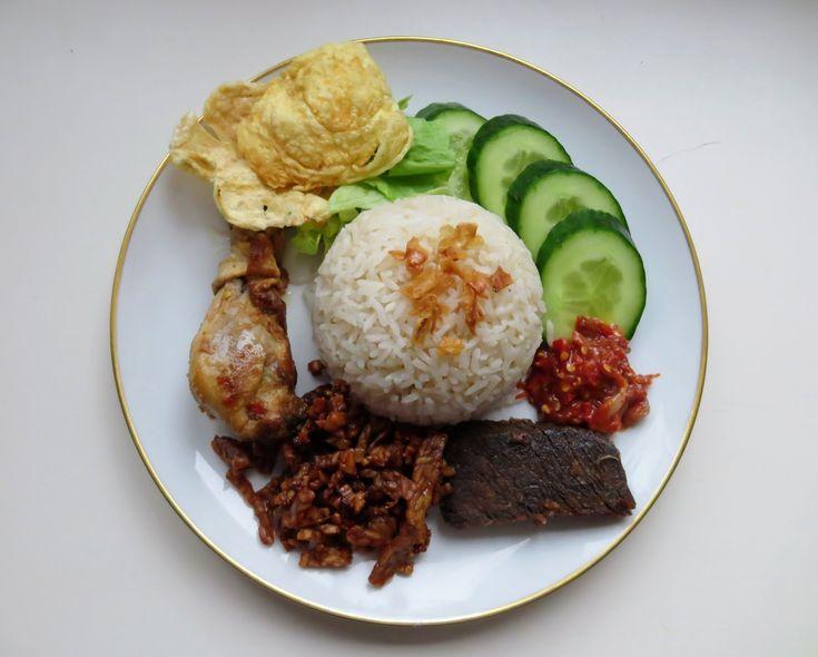 Nasi Uduk ist ein gekochter Reis im Kokosmilch und Gewürze, diese Reis-Spezialitäten aus Jakarta schmeckt herzhaft und duftet so gut. Dieser gewürzte Reis wurde in einem Teller mit vielen Beilagen  serviert.