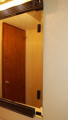 Framing a Bathroom Mirror with velcro strips.  Easy to paint trim a different color in the future.